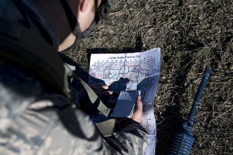 An Air Force Academy Cadet plots location points before conducting land navigation during an Air Liaison Officer Aptitude Assessment, Feb. 15, 2017, at Camp Bullis, Texas. The cadets were ambushed by cadre firing blanks multiple times during the land navigation portion of their assessment. (U.S. Air Force photo by Airman 1st Class Daniel Snider)