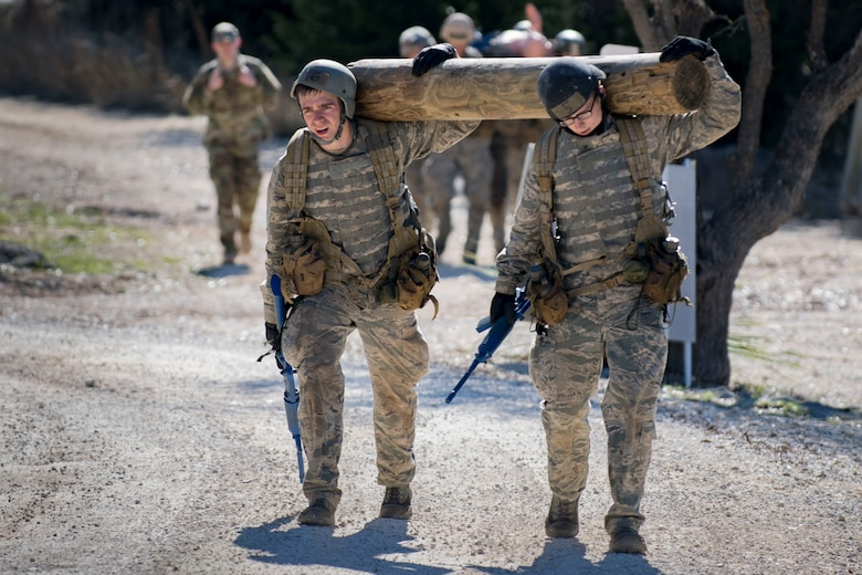 Air Force Academy cadets carry a log over their shoulders during a medical evacuation march at an Air Liaison Officer Aptitude assessment, Feb. 16, 2017, at Camp Bullis, Tx. The cadets were required to trek multiple miles carrying logs and simulated wounded to a medical evacuation zone in limited time. (U.S. Air Force photo by Airman 1st Class Daniel Snider)