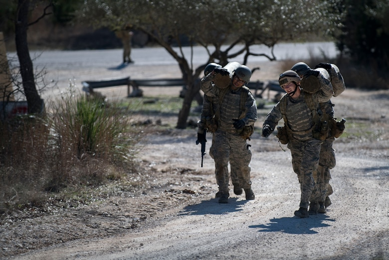 Air Force Academy cadets carry a logs over their shoulders during a medical evacuation march at an Air Liaison Officer Aptitude assessment, Feb. 16, 2017, at Camp Bullis, Texas. The cadets were required to trek multiple miles carrying logs and simulated wounded to a medical evacuation zone in limited time. (U.S. Air Force photo by Airman 1st Class Daniel Snider)