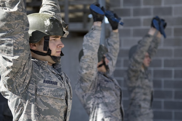 Air Force Academy Cadet Anderson holds a training rifle above his head during tasked obstacle training at an Air Liaison Officer Aptitude assessment, Feb. 14, 2017, at Camp Bullis, Texas. The cadets were divided into two groups for the tasked obstacle portion of the assessment, leaving the other group time to work out. (U.S. Air Force photo by Airman 1st Class Daniel Snider)