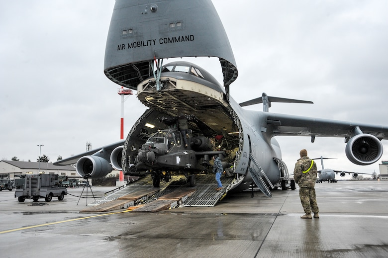 An Army AH-64 Apache helicopter is unloaded from an Air Mobility Command C-5M Galaxy at Ramstein Air Base, Germany, Feb. 22, 2017, in support of Operation Atlantic Resolve.  The four Apache helicopters that arrived are part of a larger contingent of helicopters and personnel comprising of Operation Atlantic Resolve, a U.S. commitment to maintaining peace and stability in the European region.  (U.S. Air Force photo/Staff Sgt. Timothy Moore)
