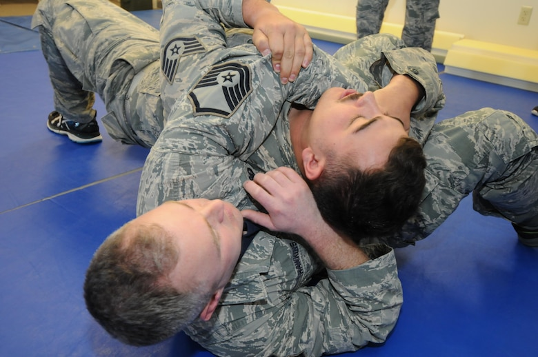 U.S. Air Force Staff Sgt. Cody Broussard, 173rd Security Forces Squadron, works against his assailant Master Sgt. Ross Hawkins, 173rd SFS, in a demonstration of Air Force Security Forces Combatives where an officer works to extract themselves from a choke hold, Jan. 13, 2017 at Kingsley Field in Klamath Falls, Oregon. Combatives training helps security forces members protect themselves in a hand-to-hand situation by using leverage to extract themselves from a bad situation or to quickly subdue an attacker without causing harm. (U.S. Air National Guard photo by Tech. Sgt. Jefferson Thompson)
