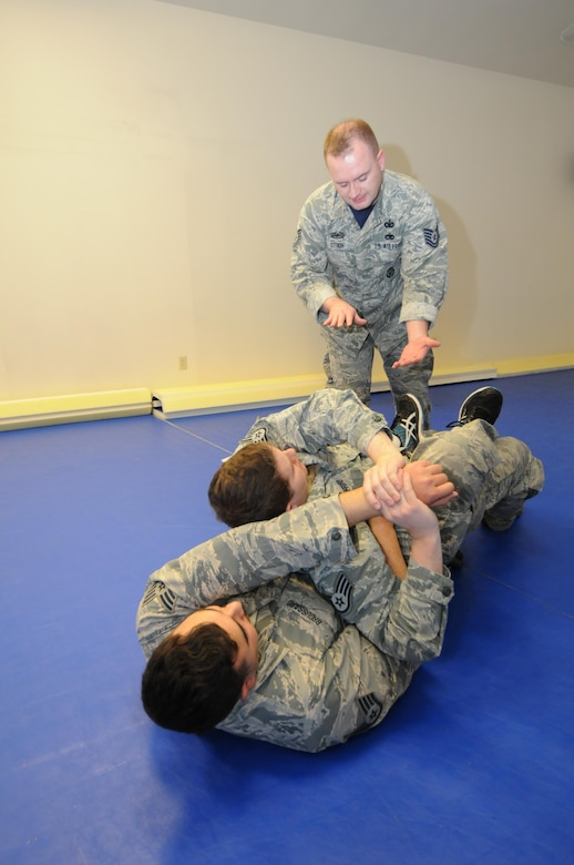 U.S. Air Force Tech. Sgt. Brandan Stroh, a combatives training instructor with the 173rd Security Forces Squadron, instructs Staff Sgt. Nathan Gifford, 173rd SFS,  on how protect himself and subdue an assailant during a hand-to-hand altercation, Jan. 13, 2017. Staff Sgt. Cody Broussard (bottom) an experienced combatives practitioner plays the role of the aggressor. (U.S. Air National Guard photo by Tech. Sgt. Jefferson Thompson)