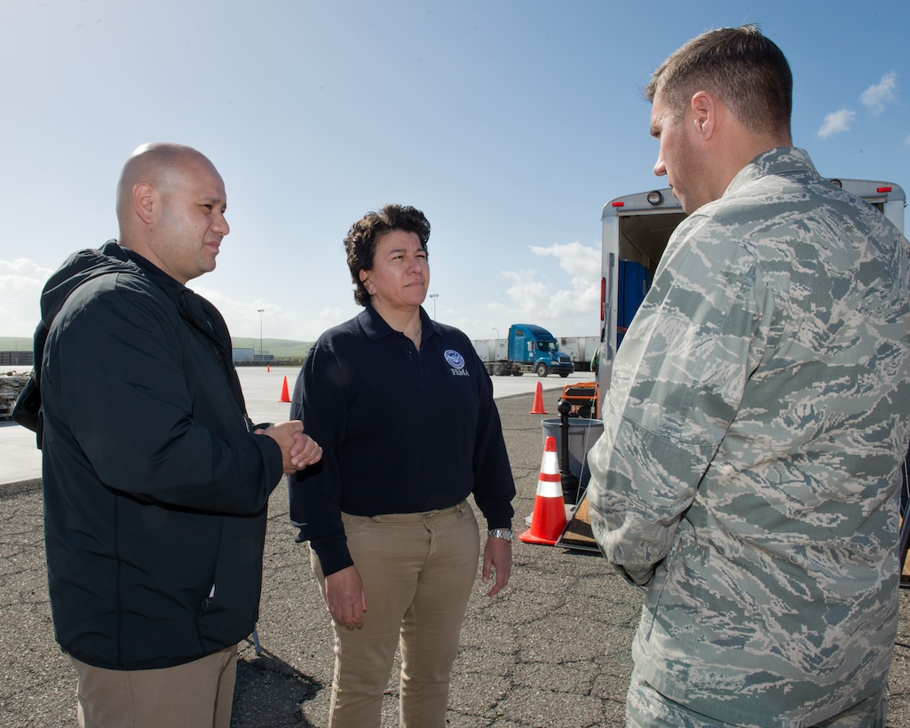 U.S. Air Force Col. John Klein, 60th Air Mobility Wing commander, talks with representatives from the Federal Emergency Management Agency at Travis Air Force Base, Calif., Feb. 16, 2017. Travis AFB is acting as a staging area for FEMA personnel, providing space for necessary equipment and supplies in case of the Oroville auxiliary spillway failure. (U.S. Air Force photo/Louis Briscese)