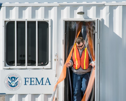 A Federal Emergency Management Agency representative exits the Logistics Mobile Office C2 Unit at Travis Air Force Base, Calif., Feb. 16, 2017. Travis AFB is acting as a staging area for FEMA personnel, providing space for necessary equipment and supplies in case of the Oroville auxiliary spillway failure. (U.S. Air Force photo/Louis Briscese)