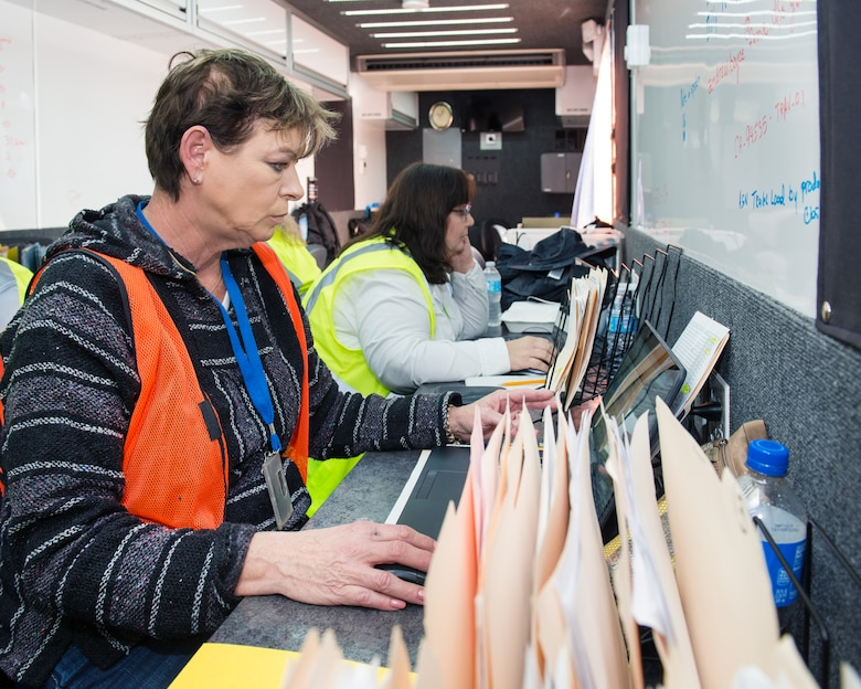 Janine Hopkins and Elizabeth Reeves, both logistics chain systems managers with the Federal Emergency Management Agency track trucks as they arrive at Travis Air Force Base, Calif., Feb. 16, 2017. Travis AFB is acting as a staging area for FEMA personnel, providing space for necessary equipment and supplies in case of the Oroville auxiliary spillway failure. (U.S. Air Force photo/Louis Briscese)