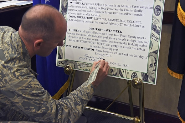 Col. Ryan Samuelson, 92nd Air Refueling Wing commander, signs the Military Saves Week proclamation Feb. 2, 2017, at Fairchild Air Force Base, Washington. Military Saves Week is an annual opportunity held in February for installations and organizations to promote good savings behavior and a chance for service members and their families to assess their own saving status. (U.S. Air Force photo/Senior Airman Mackenzie Richardson)
