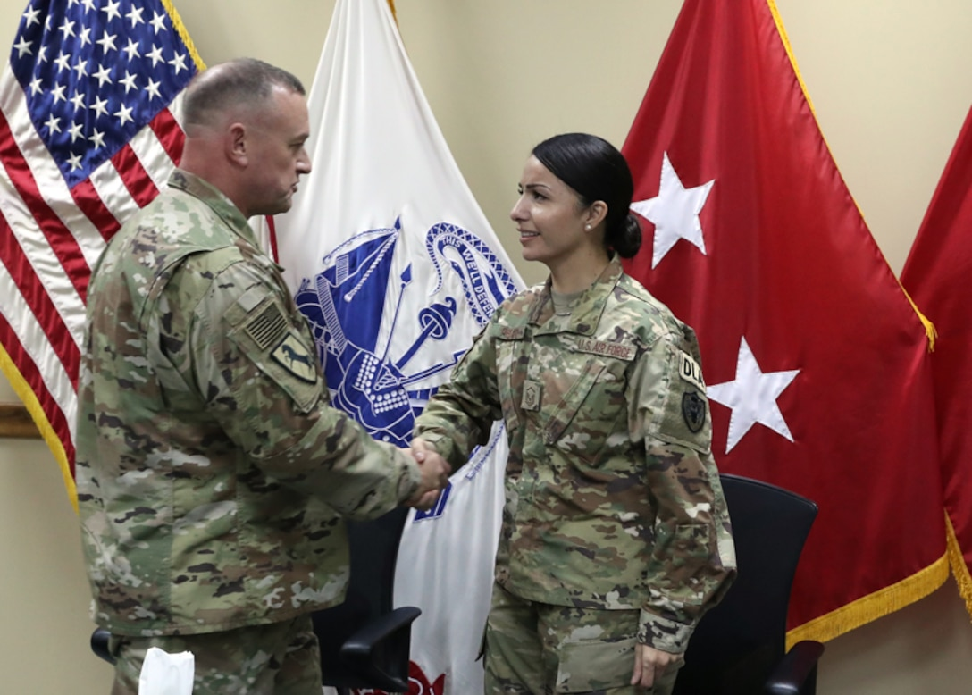 316th Expeditionary Sustainment Command Commanding General Army Brig. Gen. Robert Harter honors Air Force Tech. Sgt. Janet Pelayo, Defense Logistics Agency Aviation, with his coin at her promotion ceremony Jan 31, 2017 held at Camp Arifjan, Kuwait.