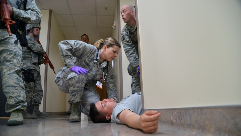 Major Allison Bradshaw, 377 Aerospace Medicine Squadron operational medicine flight commander, tends to a patient while under security forces escort during an active shooter exercise at the 377 Medical Group clinic Feb. 21. Because of the nature of the exercise, medics had to triage the patients before rendering medical care. (U.S. Air Force Photo/Senior Airman Chandler Baker)