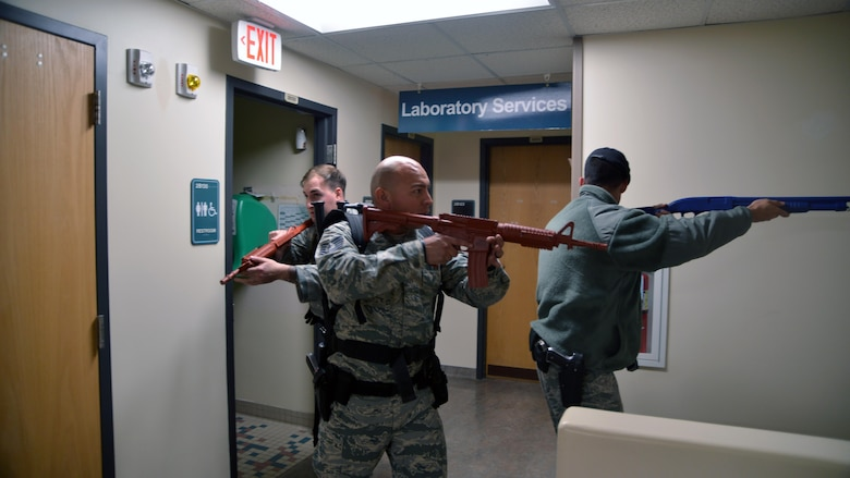 Defenders from the 377 Security Forces Squadron clear hallways inside the 377 Medical Group Clinic during an active shooter exercise Feb. 21. It took defenders 15 minutes to locate and disarm the shooter during the exercise. (U.S. Air Force Photo/ Senior Airman Chandler Baker)