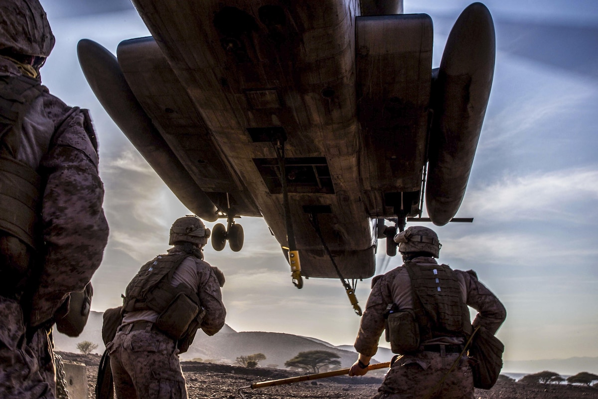 Marines stand under a hovering helicopter as they prepare to attach a barrier to it.