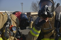 Two fire fighters with the 374th Civil Engineer Squadron perform an equipment check prior to completing a training scenario at Yokota Air Base, Japan, Feb. 16, 2017. The training helped the fire fighters gain experience and build cohesiveness to work as a better team for potential real-world scenarios. (U.S. Air Force photo by Staff Sgt. David Owsianka)