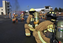 Fire fighters from the 374th Civil Engineer Squadron Fire Department look on as fire fighters from the Fussa Fire Department put out a vehicle fire during a fire training scenario at Yokota Air Base, Japan, Feb. 16, 2017. Each department went through their own tactics and procedures to put out a vehicle fire. (U.S. Air Force photo by Staff Sgt. David Owsianka)