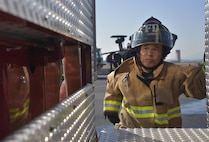 Nobuhito Takeda, 374th Civil Engineer Squadron Fire Department fire fighter, climbs up a fire truck to help unload a hose prior to completing a vehicle fire training scenario at Yokota Air Base, Japan, Feb. 16, 2017. Yokota's personnel trained with the Japan Self-Defense Force and Fussa fire departments to gain different perspectives on putting out vehicle fires. (U.S. Air Force photo by Staff Sgt. David Owsianka)