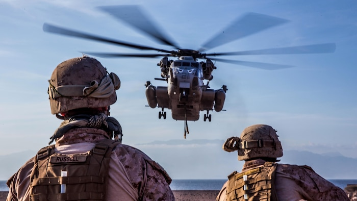 U.S. Marines Corporals Christopher Russell (left) and Sean Bensel, landing support specialists, wait for a CH-53E Super Stallion to get into position during helicopter external load training at Arta Beach, Djibouti, Feb. 16, 2017. A helicopter support team's primary mission is to attach supplies, equipment or vehicles to the external lift hooks of helicopters to transport them in an expedient manner. Russell and Bensel are with Combat Logistics Battalion 11 and the Stallion and crew are with Marine Medium Tiltrotor Squadron 163 (Reinforced), 11th Marine Expeditionary Unit.