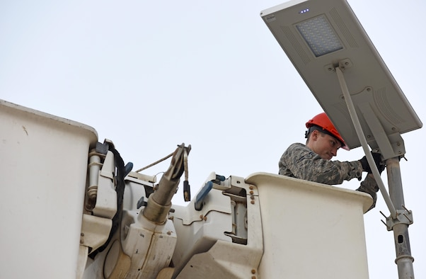 U.S. Air Force Airman 1st Class Corey Martin, an electrical systems apprentice with the 379th Expeditionary Civil Engineer Squadron, adjusts a light fixture at Al Udeid Air Base, Qatar, Feb. 22, 2017. This particular light fixture was a solar-powered low-emitting diode light that collects the sun's energy during the day and stores it in a rechargeable battery cell.  (U.S. Air Force photo by Senior Airman Cynthia A. Innocenti)