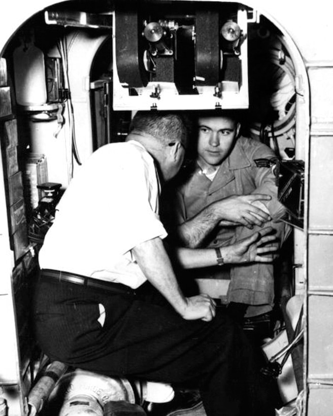 Airman 1st Class Donald G. Farrell, talks with Fenten Duepner, an electronic engineer at the Air Force School of Aviation Medicine, during a pre-ascension briefing at Randolph Air Force Base. Farrell is inside the small shell in which he began a seven-day journey into the unknown on Feb. 9, 1958. The space cabin is designed to duplicate the conditions Farrell might encounter if he were on a trip to the moon. 