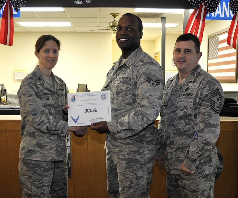 "Senior Airman Michael Lindsay, 47th Force Support Squadron reenlistments and extensions technician (center), accepts the ""XLer of the Week"" award from Col. Michelle Pryor, 47th Flying Training Wing vice commander (left), and Chief Master Sgt. George Richey, 47th FTW command chief (right), on Laughlin Air Force Base, Texas, Feb. 15, 2017. The XLer is a weekly award chosen by wing leadership and is presented to those who consistently make outstanding contributions to their unit and Laughlin. (U.S. Air Force photo/Technical Sgt. Mike Meares)"
