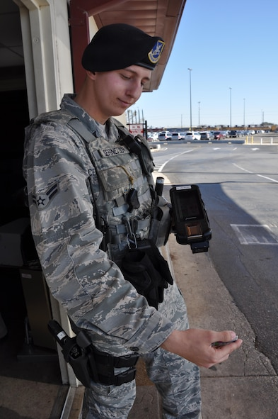 A1C Travis Cernetisch, assigned to the 802nd Security Forces Squadron, uses the latest Defense Biometrics Identification System (DBIDS) equipment to scan driver's identification at JBSA-Lackland Kelly annex.  Airmen around the country are using the system to DBIDS as an enhanced security system used to monitor entry onto military installations. (US Air Force Photo/Annette Crawford)