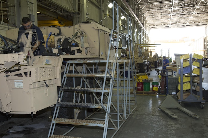 Teodoro Huerta, a former Army staff sergeant who has been deployed to the Middle East, is a heavy mobile equipment mechanic on the LVSR AMKR line at Production Plant Barstow, Marine Depot Maintenance Command. He is installing hydraulic lines on the AMKR at the plant, Feb. 14.