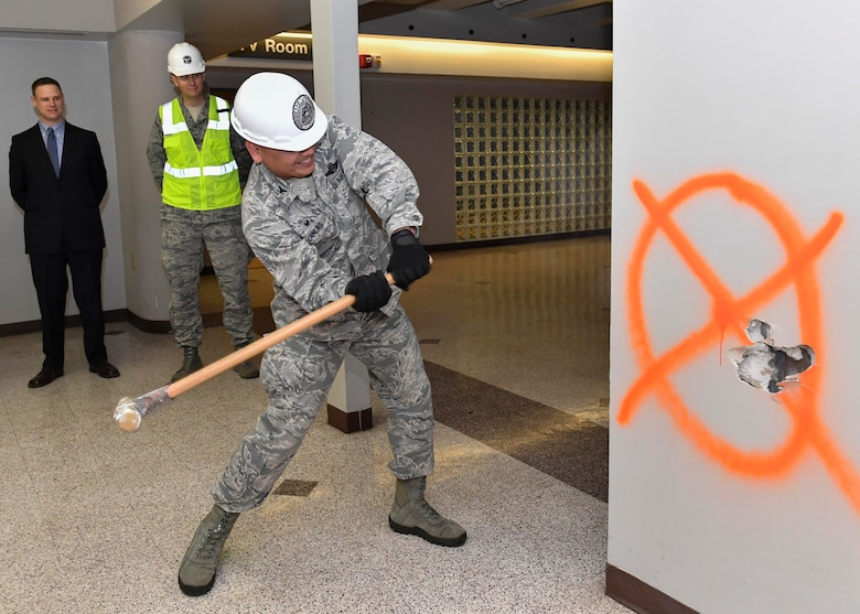 Col. Jimmy Canlas, 437th Airlift Wing commander, swings a sledgehammer to start construction of the new 437th Aerial Port Squadron Passenger Terminal here, Feb. 23, 2017. The passenger terminal is being renovated to improve the facility by adding a new fire suppression system, roof, utility systems, restrooms inside the gated area and a redesigned family room. The passenger terminal will operate out of a temporary facility until construction is complete. Signage is in place to direct passengers and base personnel from the old terminal to the temporary location.