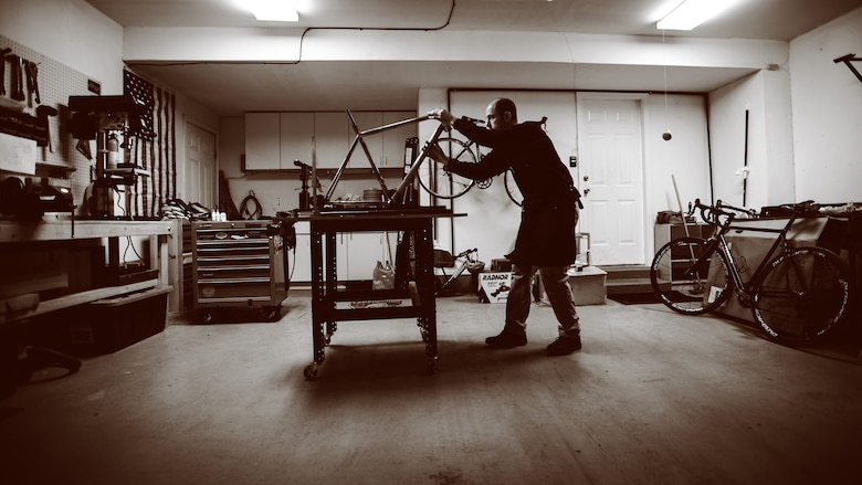 Air Force 1st Lt. Ken Cerreta checks the alignment on a handmade bicycle frame. Cerreta began building custom steel frames in 2014. (Paul Holcomb/U.S. Air Force)