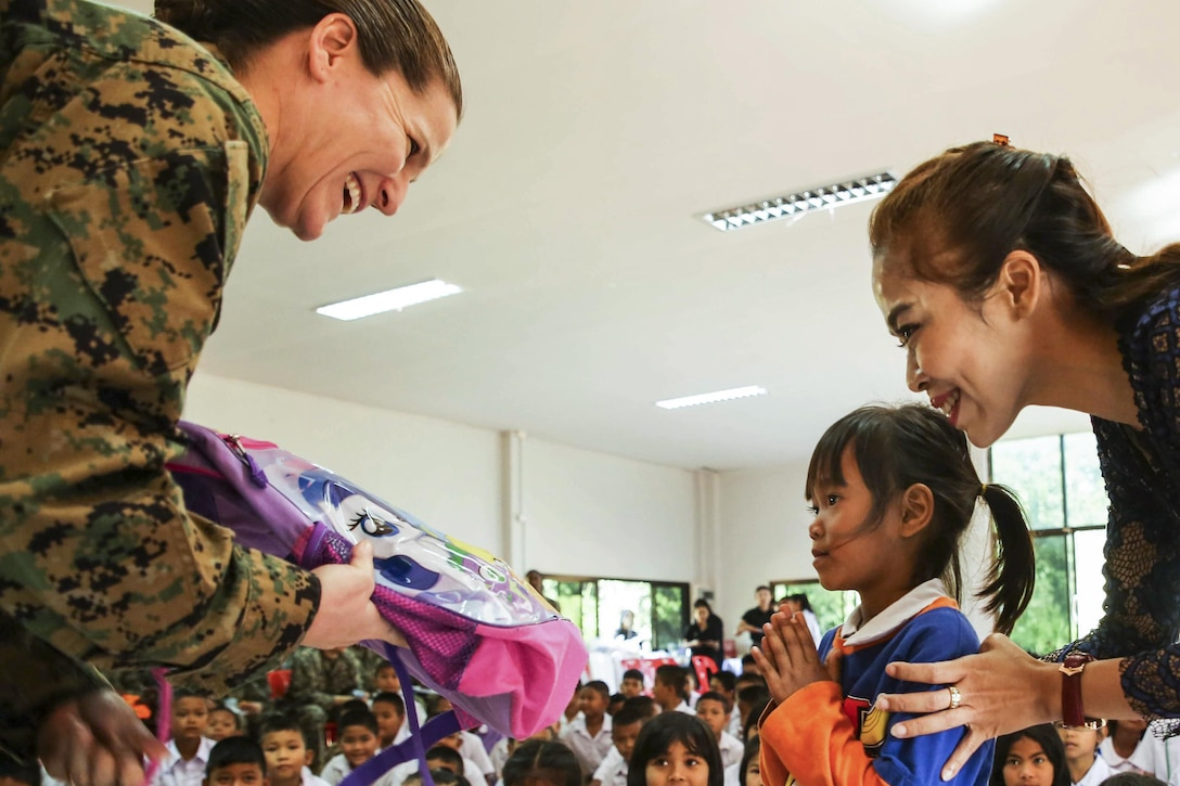 Marine Corps Col. Maria McMillen gives school supplies to a Thai girl at a school in Chanthaburi, Thailand
