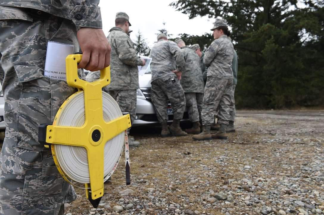 Staff Sgt. Jesse Reyes, 627th Security Forces Squadron combat arms instructor, holds measuring tape prior to the 627th Civil Engineer Squadron's land navigation training on Joint Base Lewis-McChord, Wash., Feb. 16, 2017. More than 50 627th CES Airmen participated in the training here where they learned map orientation, grade ordinates and how to use an azimuth. (U.S. Air Force photo/Staff Sgt. Naomi Shipley)