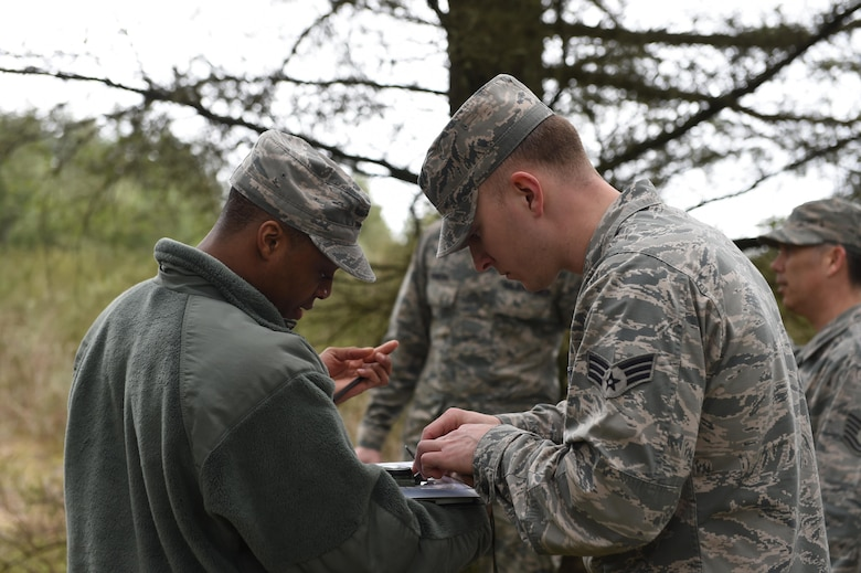 Members of the 627th Civil Engineer Squadron conduct land navigation training on Joint Base Lewis-McChord, Wash., Feb. 16, 2017. 50 Airmen were split up into nine teams and used a compass and azimuth to navigate to three different coordinates and back to the start. (U.S. Air Force photo/Staff Sgt. Naomi Shipley)