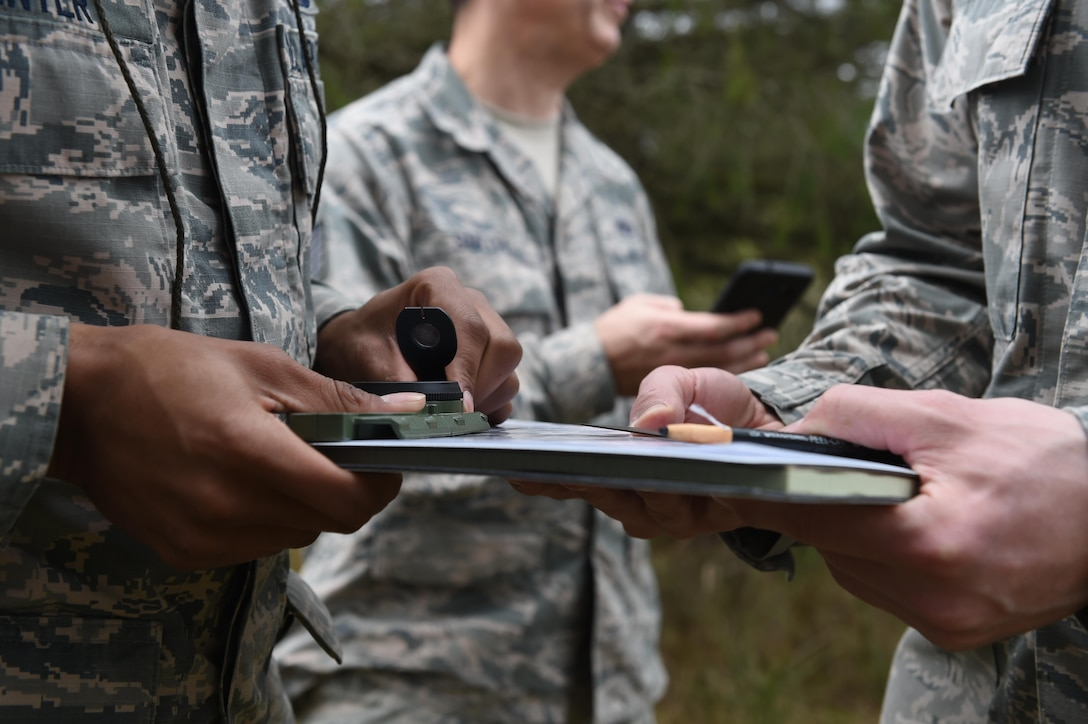 Airmen from the 627th Civil Engineer Squadron hold an azimuth and map during land navigation training on Joint Base Lewis-McChord, Wash., Feb. 16, 2017. The 627th CES typically conducts joint land navigation and convoy training with the Army prior to deployments where they will be working outside the wire, but this time they teamed up with the 627th Security Forces Squadron. (U.S. Air Force photo/Staff Sgt. Naomi Shipley)