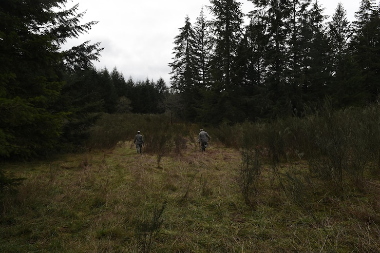 Members of the 627th Civil Engineer Squadron walk through thick brush on Joint Base Lewis-McChord, Wash., Feb. 16, 2017. The team traveled more than 1,500 meters in approximately two hours to reach their three coordinates using a compass, map and azimuth. (U.S. Air Force photo/Staff Sgt. Naomi Shipley)