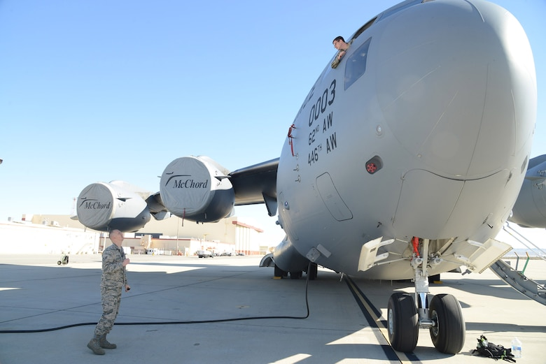 Staff Sgt. Steven Schrader (left) and Staff Sgt. Alex Rini, 412th Logistics Test Squadron, discuss the progress of the C-17 portion of the Hybrid Electric Flightline Cart Technology Pathfinder tests. The nearly zero noise of the HEF allows maintainers to converse without the use of the aircraft's internal communication system. (U.S. Air Force photo by Christopher Ball)