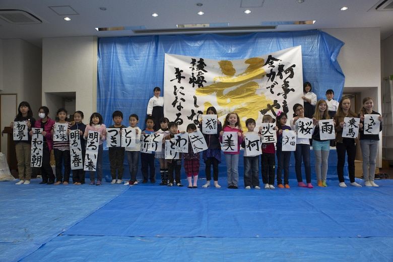 Children from Marine Corps Air Station Iwakuni and Japanese local children pose for a photo with their completed art work during a calligraphy event in Waki Town, Japan, Jan. 7, 2017. The children learned how to write their goals in Kanji for the new year. Similar to the American tradition of New Year's resolutions, the Japanese use calligraphy to write their goals at the beginning of every new year.   (U.S. Marine Corps photo by Lance Cpl. Joseph Abrego)