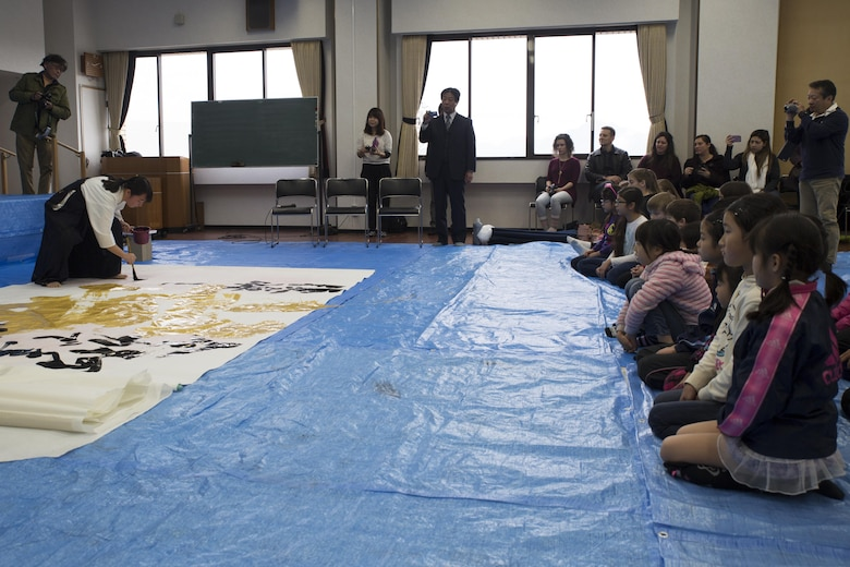 Marine Corps Air Station Iwakuni residents and Japanese locals watch as a member of the Otake Senior High School performs calligraphy in Waki Town, Japan, Jan. 7, 2017. Similar to the American tradition of New Year's resolutions, the Japanese use calligraphy to write their goals at the beginning of every new year.  (U.S. Marine Corps photo by Lance Cpl. Joseph Abrego)