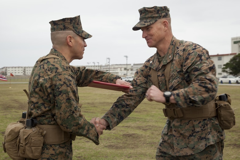 Sgt. Maj. Max Garcia, left, and Lt. Col. Siebrand Niewenhous IV, shake hands during a relief and appointment ceremony at Camp Hansen, Okinawa, Japan, Feb. 24, 2017. Sgt. Maj. Christopher Gasser relieved Garcia during the ceremony, assuming duties as senior enlisted advisor at Combat Logistics Battalion 31. (U.S. Marine Corps photo by Lance Cpl. Amy Phan/Released)