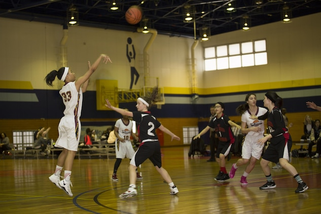 Sakura Fleming, left, a forward for Matthew C. Perry High School's Lady Samurai basketball team, takes a shot against a defender during the 2017 Division 2 Girls' Basketball Tournament at the IronWorks Gym on Marine Corps Air Station Iwakuni, Japan, Feb. 22, 2017. M.C. Perry High School hosted 11 teams from the Far East Division for the tournament. The teams endured two days of physically demanding competition for the opportunity at a championship game in a double elimination style tournament. (U.S. Marine Corps photo by Lance Cpl. Joseph Abrego)
