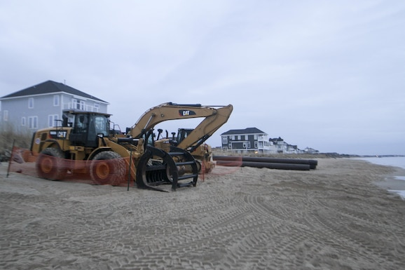Heavy equipment is staged along the beach in Norfolk, Virginia's East Ocean View neighborhood. Contractors will use the equipment to move dredged up sand on the beach to create a 60 foot wide beach berm that slopes to 5 feet above mean low water. Engineers' designed the beach to absorb the wave energy, protecting critical infrastructure during coastal storms. (U.S. Army photo/Patrick Bloodgood)
