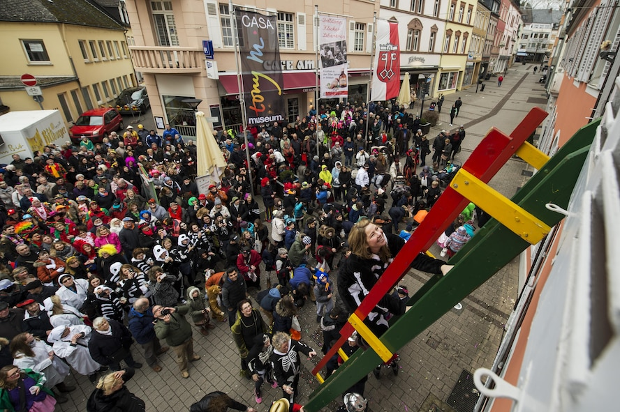 """Laura McFall, spouse of the 52nd Fighter Wing commander, climbs the ladder up to city hall during a Fasching celebration in Wittlich, Germany, Feb. 23, 2017. Once the ladies have """"taken over"""" the city hall, the celebrations begin with dancing and parading throughout the city. The traditional Fasching celebrations begin the Thursday prior to Lent at the 11th minute past the 11th hour, continue until Ash Wednesday and allow people to indulge before the Lent season. (U.S. Air Force photo by Staff Sgt. Jonathan Snyder)"""