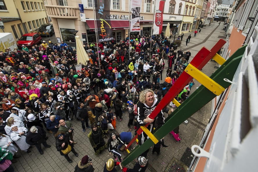 "Heather Horton, spouse of the 52nd Fighter Wing vice commander, climbs the ladder up to city hall during a Fasching celebration in Wittlich, Germany, Feb. 23, 2017. Once the ladies have ""taken over"" the city hall, the celebrations begin with dancing and parading throughout the city. The traditional Fasching celebrations begin the Thursday prior to Lent at the 11th minute past the 11th hour, continue until Ash Wednesday and allow people to indulge before the Lent season. (U.S. Air Force photo by Staff Sgt. Jonathan Snyder)"