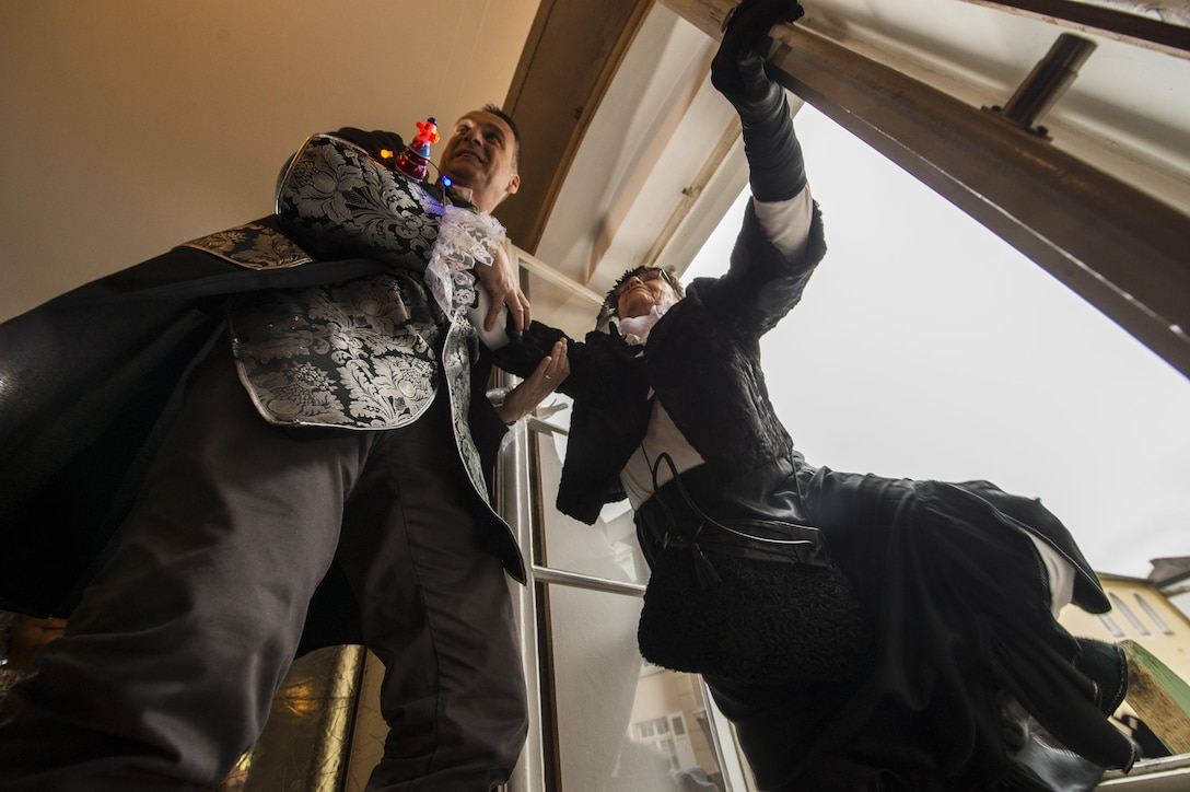 "Joachim Rodenkirch, left, mayor of Wittlich, helps a local German woman through a window at city hall during a Fasching celebration in Wittlich, Germany, Feb. 23, 2017. Once the ladies have ""taken over"" the city hall, the celebrations begin with dancing and parading throughout the city. The traditional Fasching celebrations begin the Thursday prior to Lent at the 11th minute past the 11th hour, continue until Ash Wednesday and allow people to indulge before the Lent season. (U.S. Air Force photo by Staff Sgt. Jonathan Snyder)"