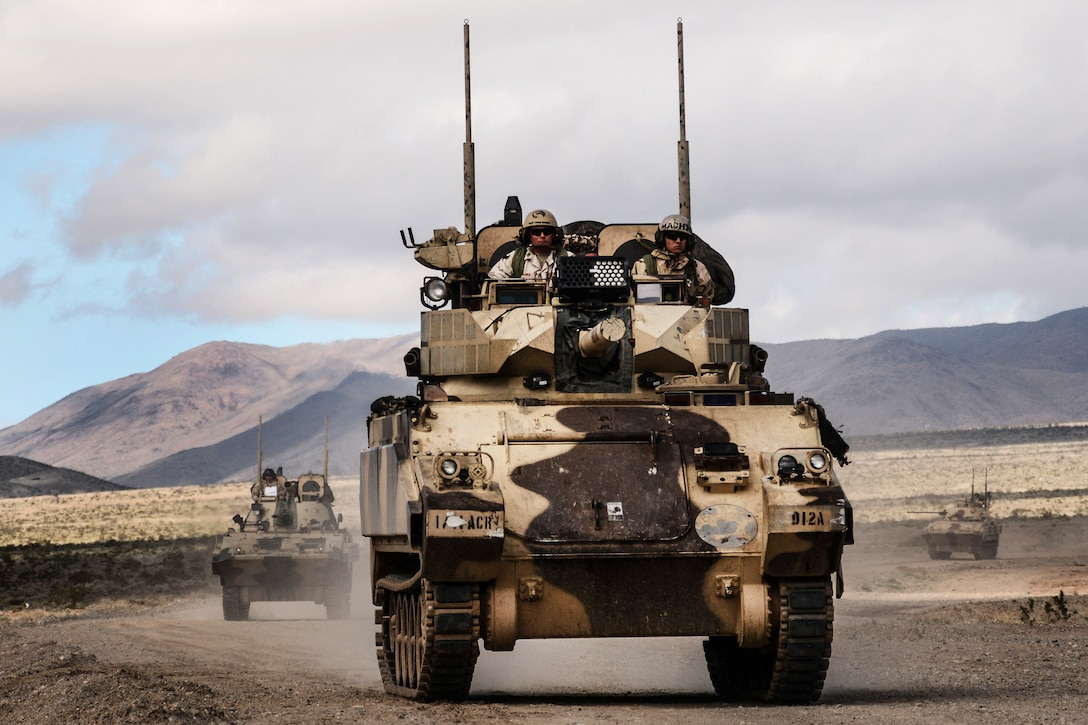 A main battle tank and infantry fighting vehicles approach the town of Barasu at the National Training Center, Fort Irwin, Calif., Feb. 20, 2017, while attempting to recapture the city held by the 1st Cavalry Division's 2nd Armored Brigade Combat Team. Army photo by Pvt. Austin Anyzeski