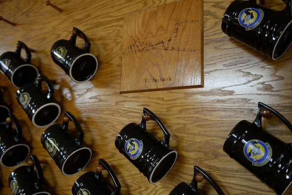 Mugs belonging to 48th Flying Training Squadron personnel hang on the wall of the 48th FTS heritage room Feb. 17, 2017, on Columbus Air Force Base, Mississippi. Mugs are hung backwards for their fallen brothers and sisters. (U.S. Air Force photo by Senior Airman John Day)