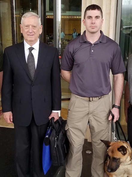 Tech. Sgt. Karl Stefanowicz, 14th Security Forces Squadron Kennel Master, and Military Working Dog Nnora pause for a photo with James Mattis, U.S. Secretary of Defense, downrange. Stefanowicz is deployed to an undisclosed location. (Courtesy photo illustration)