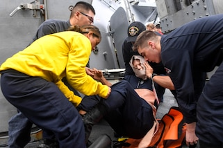 Sailors transfer a mock patient onto a stretcher during a mass casualty drill aboard the USS Wayne E. Meyer in the Pacific Ocean, Feb. 16, 2017. Navy photo by Petty Officer 3rd Class Kelsey L. Adams