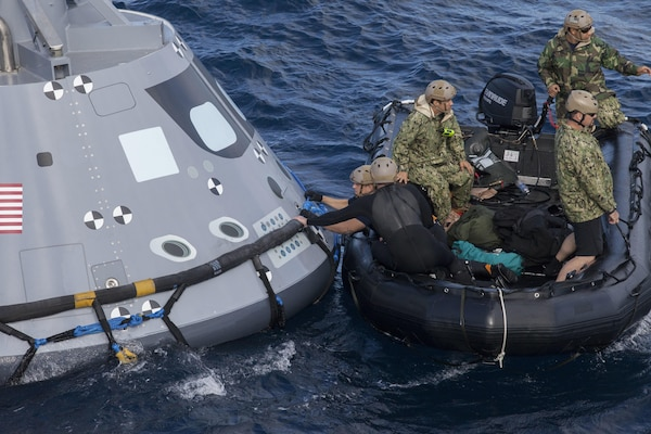 U.S. Navy divers and other personnel in a Zodiac boat secure a harness around a test version of the Orion crew module during Underway Recovery Test 5 in the Pacific Ocean off the coast of California on Oct. 28, 2016. Members of the New York Air National Guard's 106th Rescue Wing will participate in a mission in Hawaii designed to test space capsule recovery techniques and equipment, although they will not work with a capsule simulator like this one.Orion is the exploration spacecraft designed to carry astronauts to destinations not yet explored by humans.