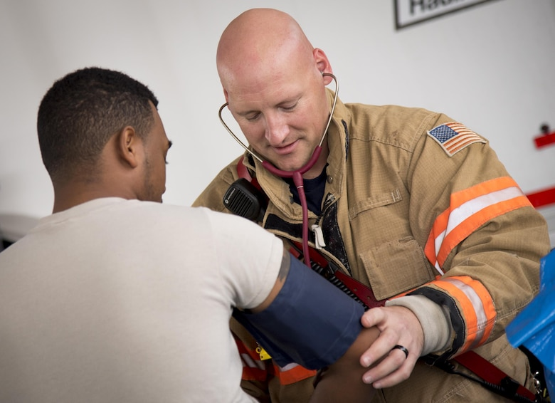 Jerry Carlton, a 96th Test Wing firefighter, checks blood pressure and pulse of Airman 1st Class Donel Wanton, 96th Aerospace Medicine Squadron, before suit up time during the hazardous material portion of an exercise Feb. 22 at Eglin Air Force Base, Fla.  The chemical, biological, nuclear response exercise tested the procedures of emergency response, explosive ordnance disposal, disaster management and bioenvironmental agencies among others.  (U.S. Air Force photo/Samuel King Jr.)