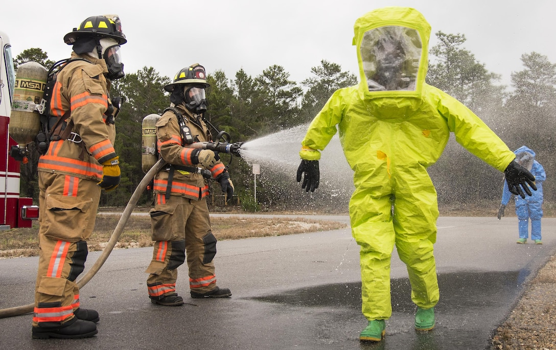 Firefighters from the 96th Test Wing hose down Airmen as part of the decontamination process at the end of a hazardous material portion of an exercise Feb. 22 at Eglin Air Force Base, Fla.  The chemical, biological, nuclear response exercise tested the procedures of emergency response, explosive ordnance disposal, emergency management and bioenvironmental agencies among others.  (U.S. Air Force photo/Samuel King Jr.)
