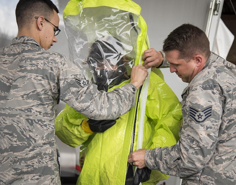 Airmen help Staff Sgt. Vikki Flores, 96th Civil Engineer Group, into her protective suit during a hazardous material portion of an exercise Feb. 22 at Eglin Air Force Base, Fla.  The chemical, biological, nuclear response exercise tested the procedures of emergency response, explosive ordnance disposal, emergency management and bioenvironmental agencies among others.  (U.S. Air Force photo/Samuel King Jr.)