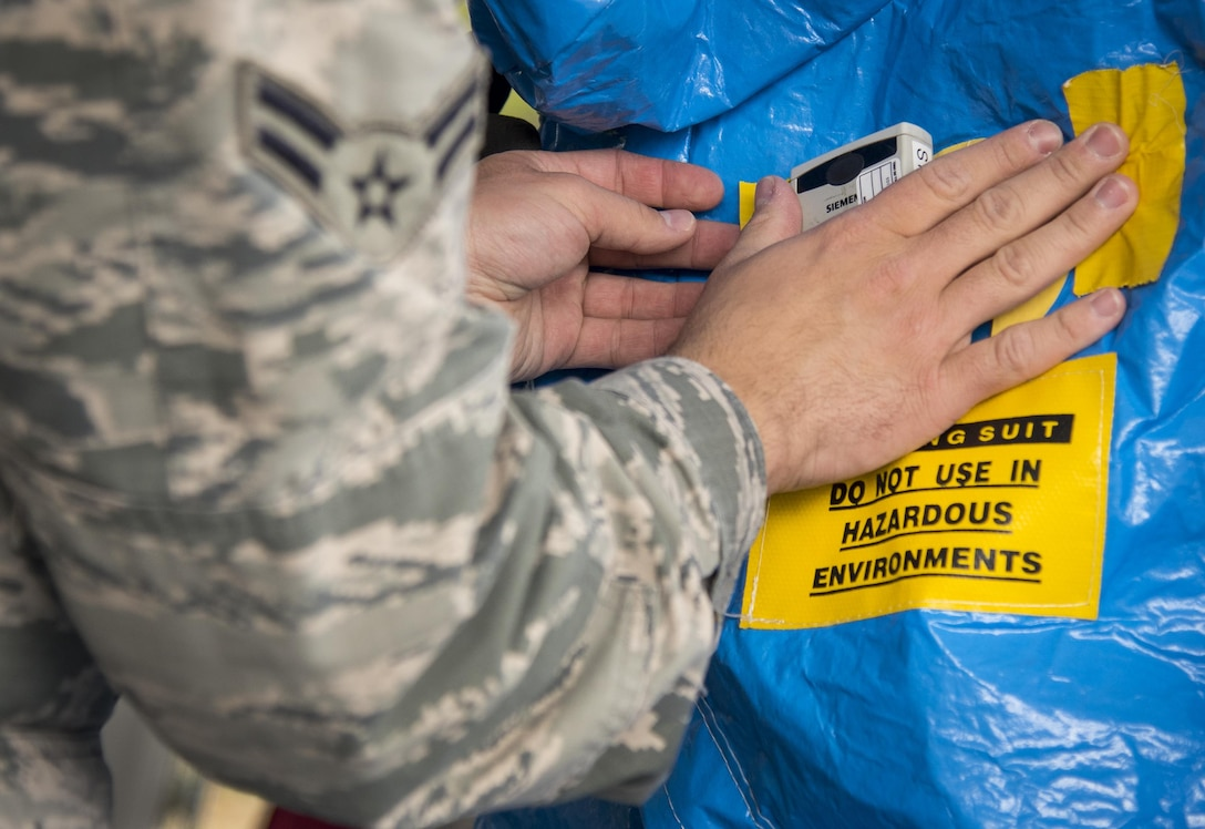 A radiation-detecting dosimeter is placed on the outside of a protective suit during a hazardous material portion of an exercise Feb. 22 at Eglin Air Force Base, Fla.  The chemical, biological, nuclear response exercise tested the procedures of emergency response, explosive ordnance disposal, disaster management and bioenvironmental agencies among others.  (U.S. Air Force photo/Samuel King Jr.)