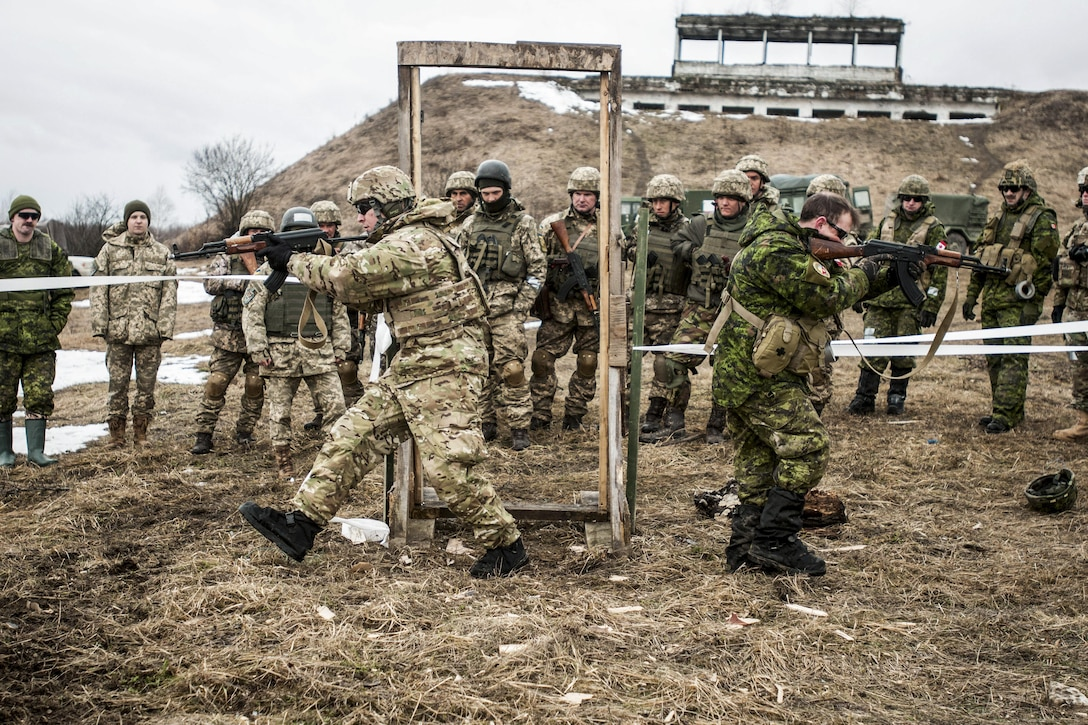 U.S. and Canadian soldiers show Ukrainian combat engineers how to clear a room while training outside.
